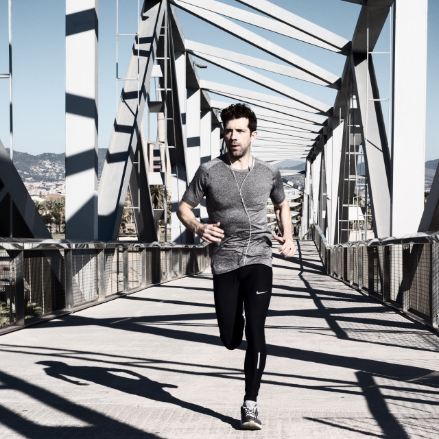 """young man running by metal bridge"" stock image"