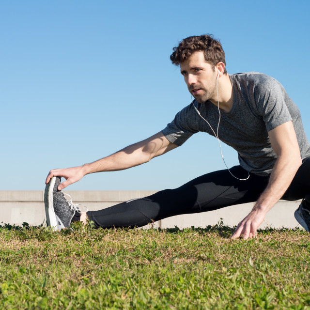 """man stretches leg in the ground"" stock image"