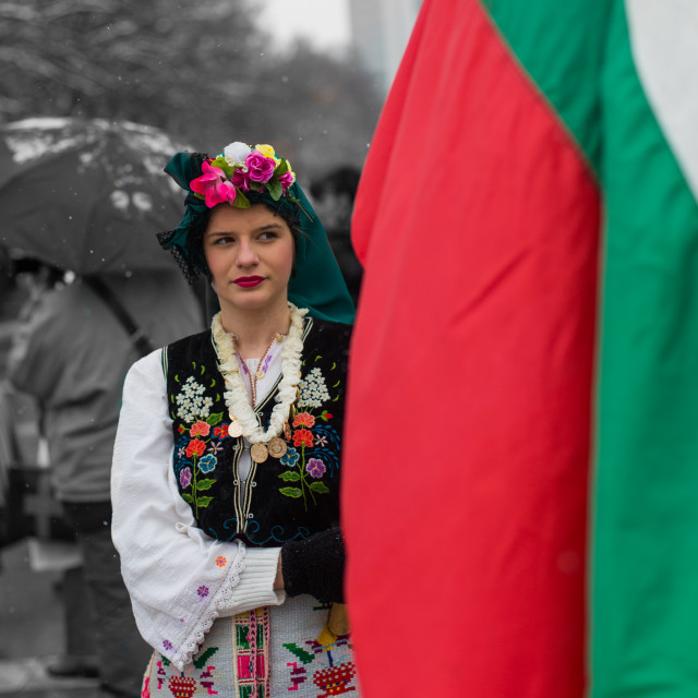 """Beautiful girl in a traditional costume holding the Bulgarian flag"" stock image"