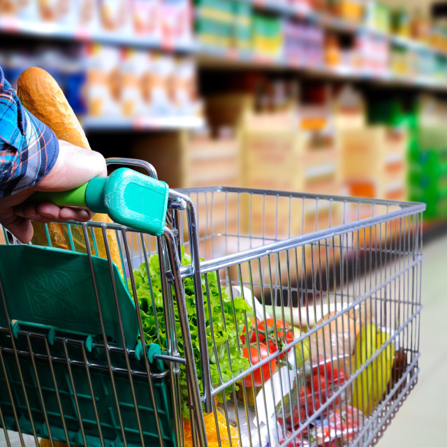 """Man pushing shopping cart in the supermarket aisle"" stock image"