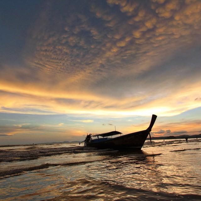 """""""Man pulling his boat into shore at ao nang beach"""" stock image"""