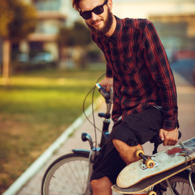 """""""Man in sunglasses riding a bike on city street"""" stock image"""