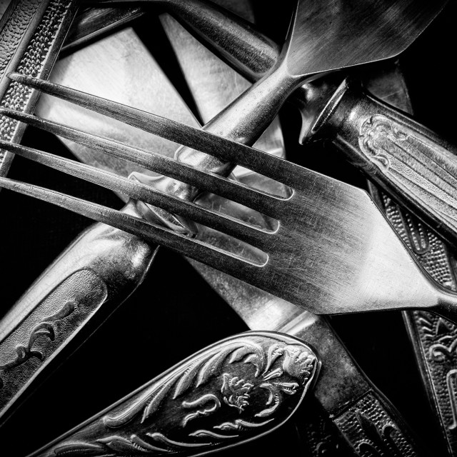 """Abstract black and white photo of mixed silver forks, spoons and"" stock image"