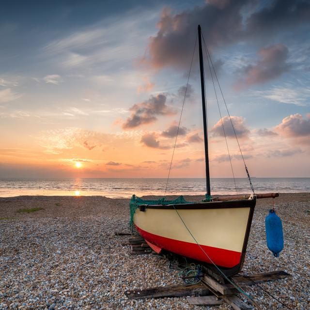 """Sailing boat under a beautiful sunrise on a shingle beach"" stock image"