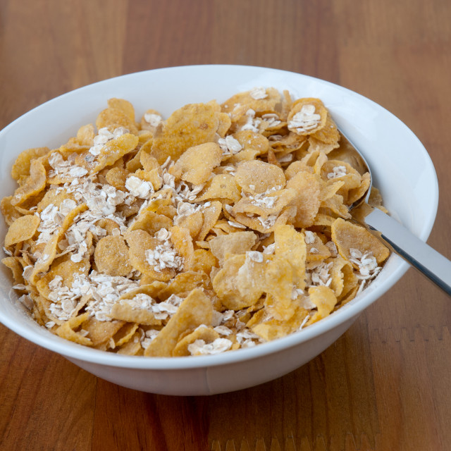 """""""White bowl with a spoon, corn and oats flakes"""" stock image"""