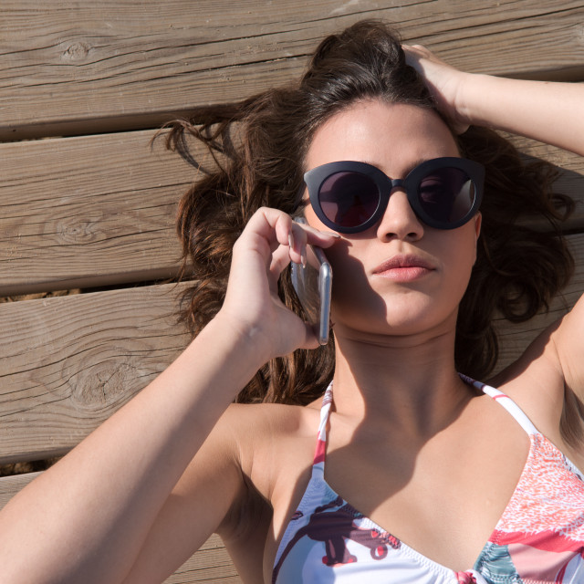"""young woman stretched listening to telephone with bikini the sun"" stock image"