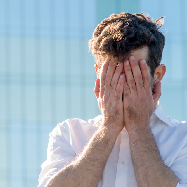 """Young Man covered his face with his hands"" stock image"