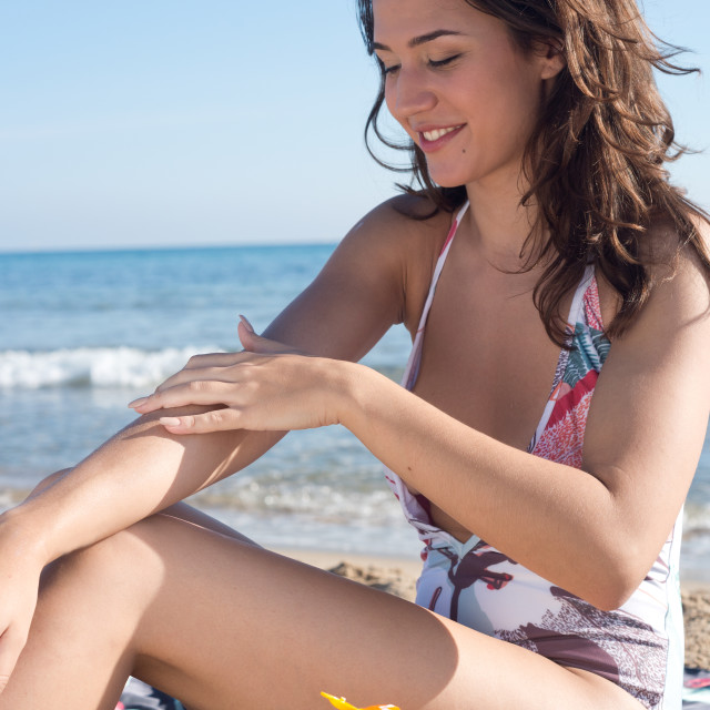 """young woman on the beach applying sunscreen"" stock image"