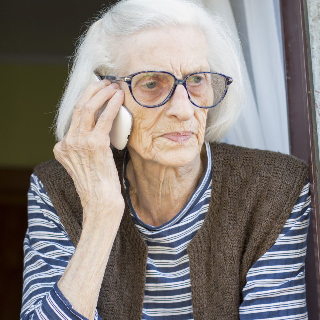 """Old grandma talking on the phone standing on her window"" stock image"