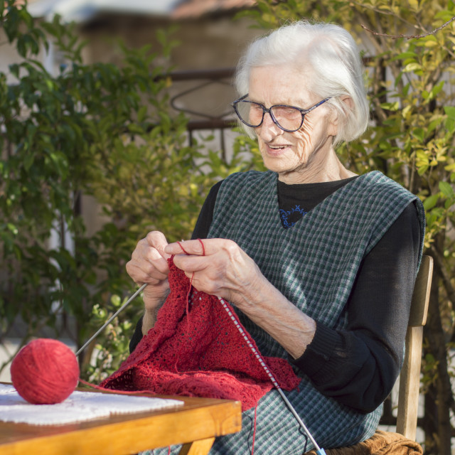 """90 years old woman knitting a red sweater"" stock image"