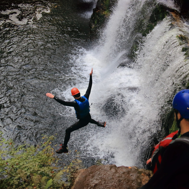 """Gorge Walker Jumping Into Waterfall."" stock image"