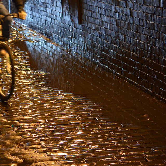 """""""Cyclist speeding through the canal underpass, on the old cobbles"""" stock image"""