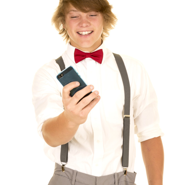 """young man in suspenders hold out phone"" stock image"