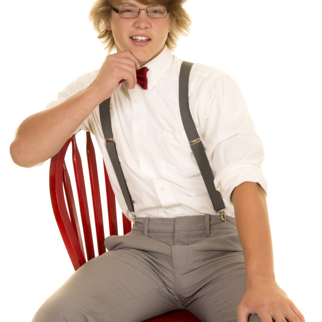 """young man in suspenders sitting on a chair hand on chin"" stock image"