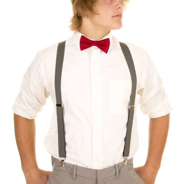 """young man in suspenders stand look to side"" stock image"