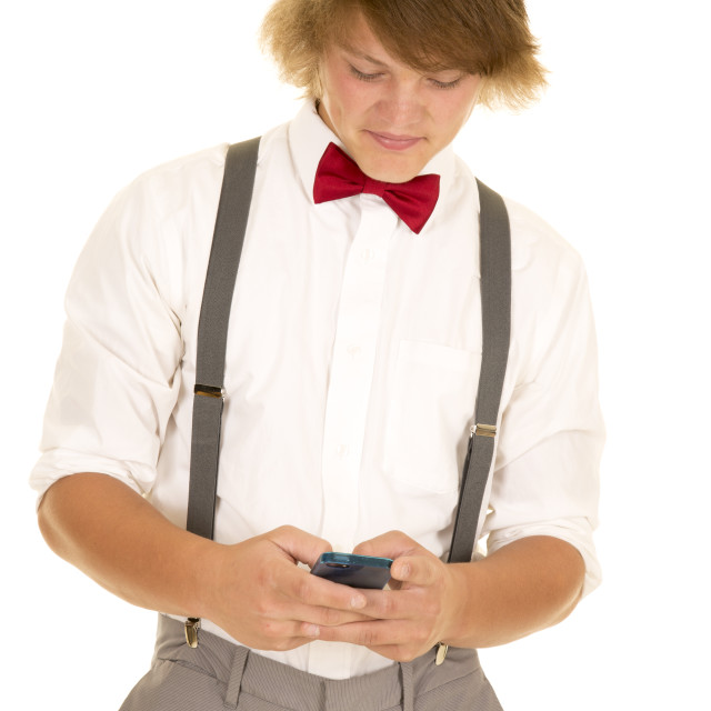 """young man in suspenders texting"" stock image"
