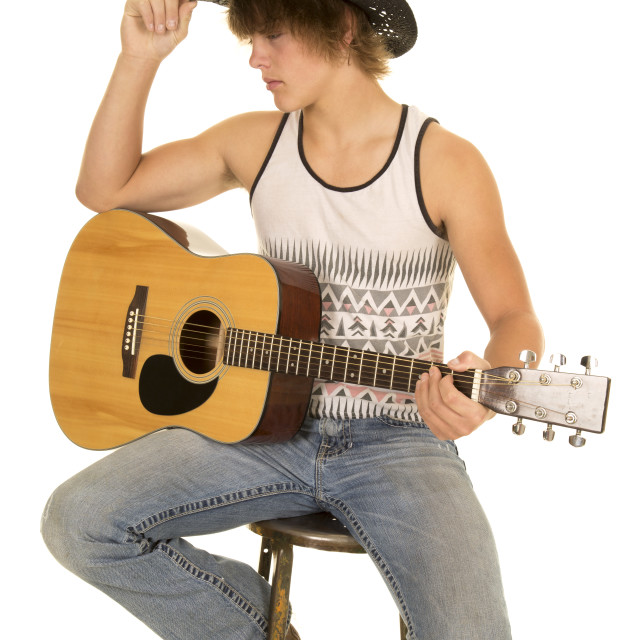 """""""young man playing a guitar with cowboy hat sit"""" stock image"""