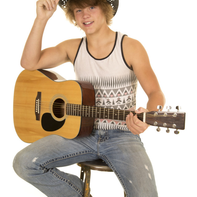 """""""young man playing a guitar with cowboy hat looking"""" stock image"""