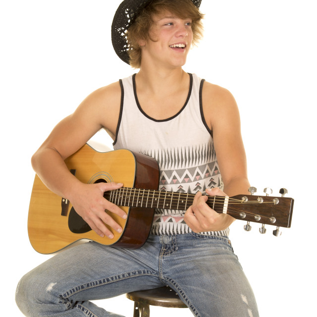 """young man playing a guitar with cowboy hat smile"" stock image"