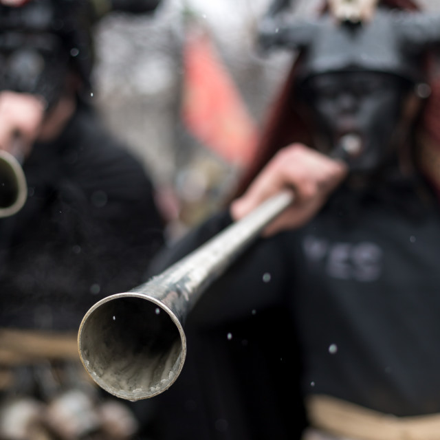 """Men with masks playing on a pipe instrument during a festival for banishing evil spirits"" stock image"