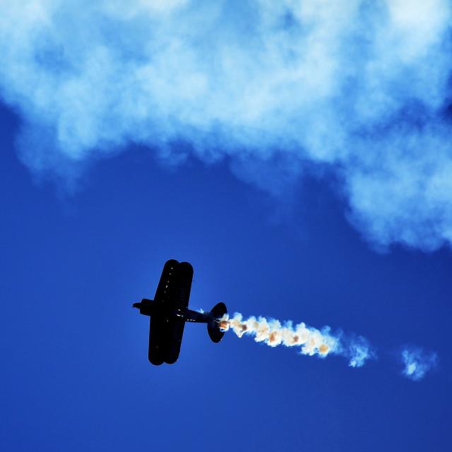 """Plane doing stunts and dropping smoke"" stock image"