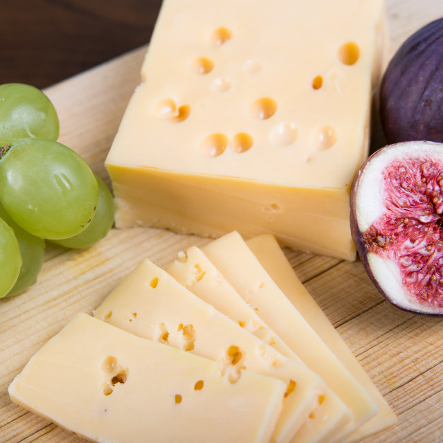 """""""Yellow cheese and fresh figs on the wooden cutting board"""" stock image"""