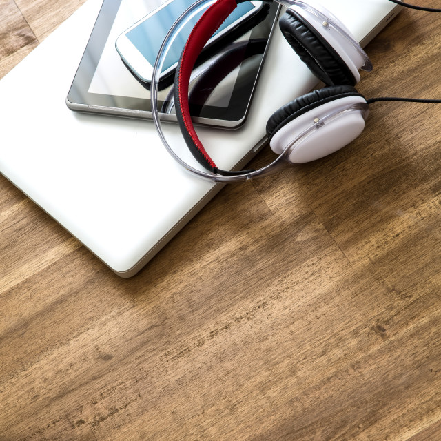 """Digital devices and Headphones on a wooden Desktop"" stock image"
