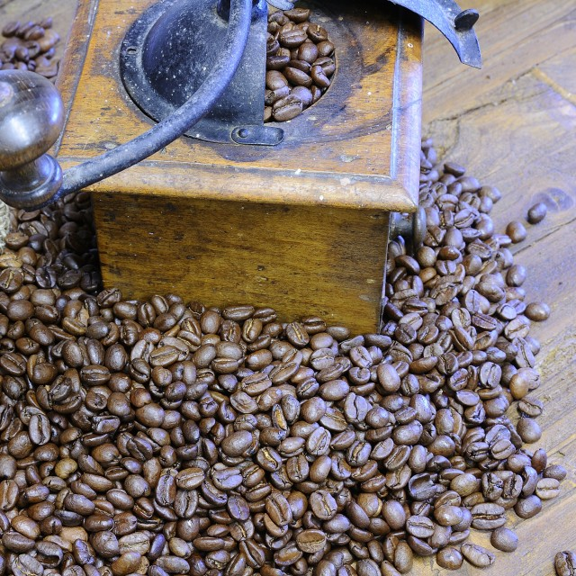 """Coffee beans and retro grinder on wooden table"" stock image"