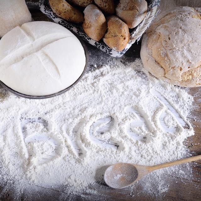 """Word 'bread' written on flour scattered on wooden table"" stock image"