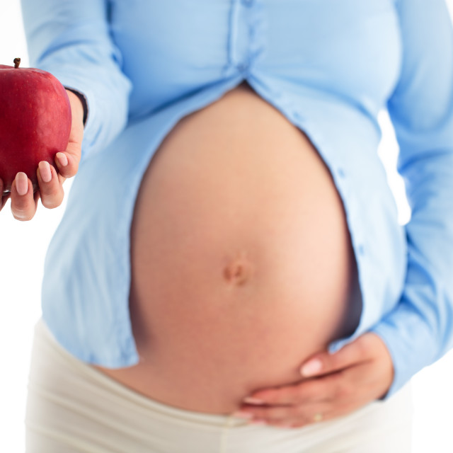 """""""Beautiful pregnant woman with a apple isolated on a white backgr"""" stock image"""