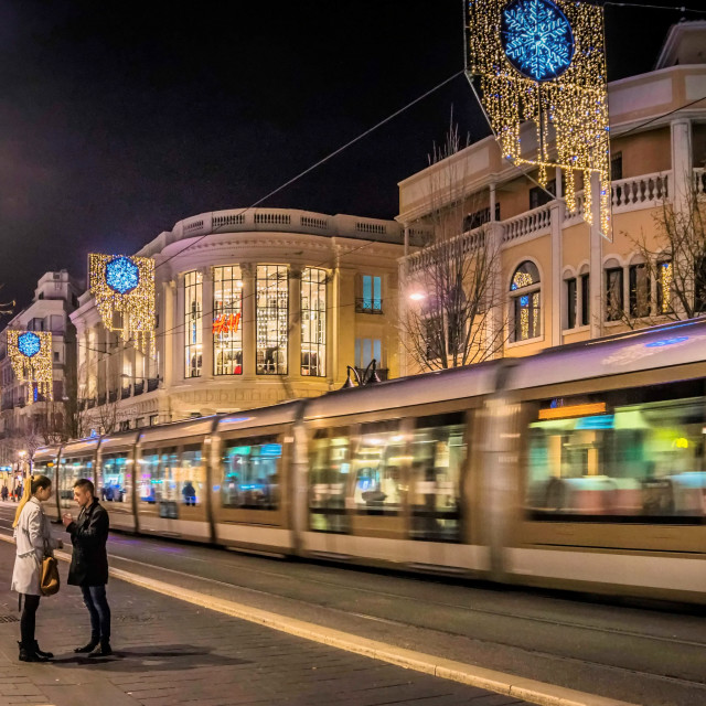 """Shopping street at night with Tram passing"" stock image"