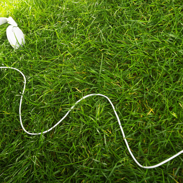 """White music earphones over green grass, studio shot"" stock image"
