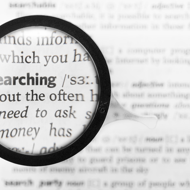 """""""Magnifying glass and dictionary definition of the word searching"""" stock image"""