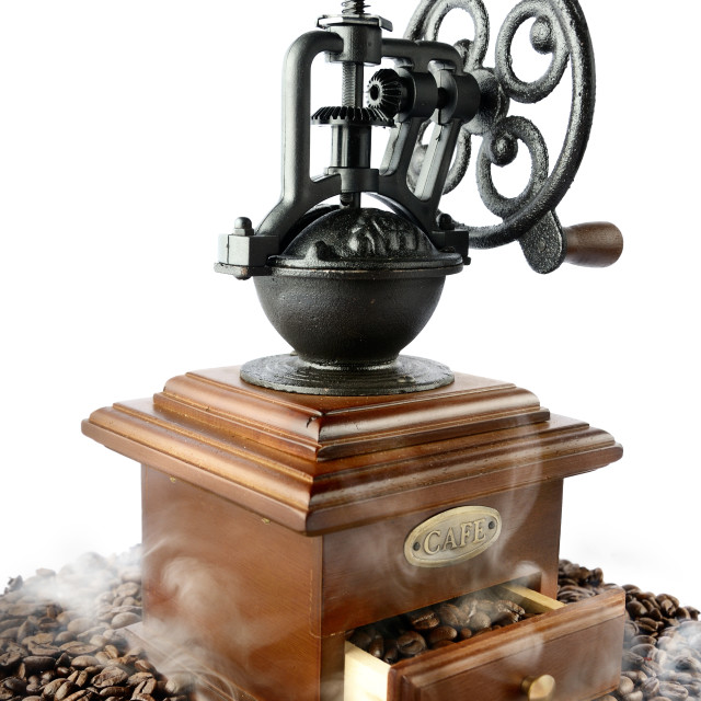 """""""old-fashioned coffee grinder with beans and smoke on white"""" stock image"""