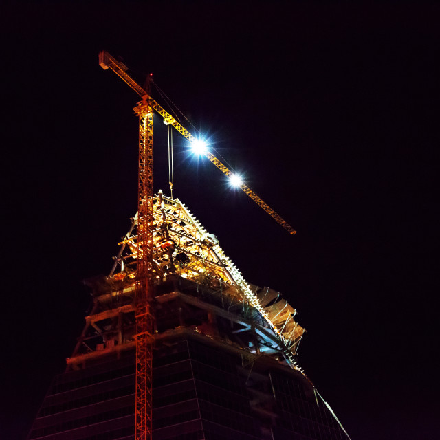 """""""Silhouette of the tower crane on the construction site with city"""" stock image"""