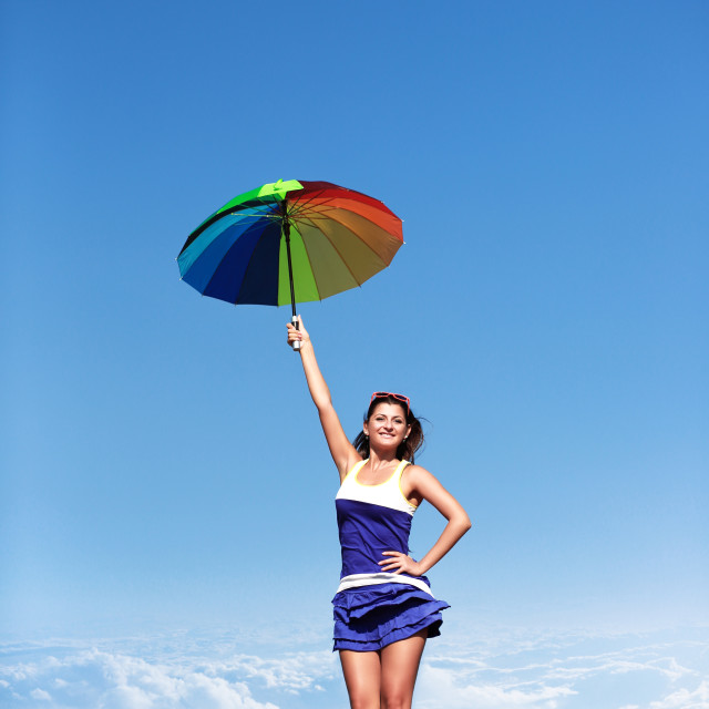 """Flying girl with colorful umbrella on the blue sky"" stock image"