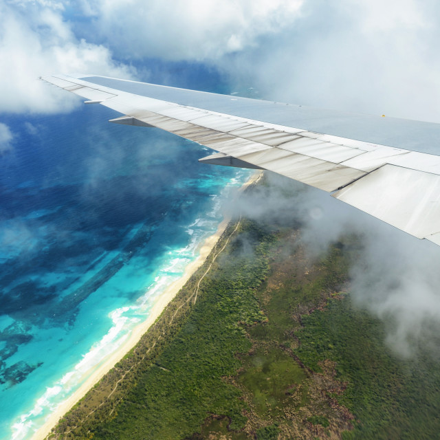 """""""Wing of an airplane flying above the clouds over tropical island"""" stock image"""