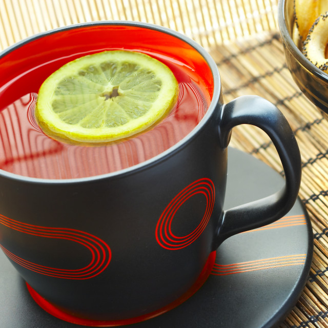 """Cup of tea with a lemon on a table"" stock image"
