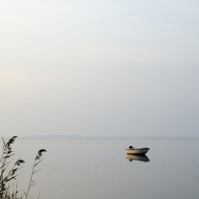 """Lone rowing boat in calm water"" stock image"