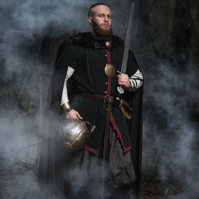 """""""Viking with sword and helmet on a background of smoky forest"""" stock image"""