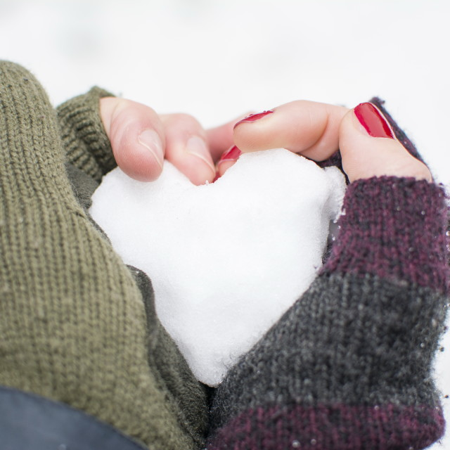 """male and female hands in gloves holding a snow shaped heart"" stock image"