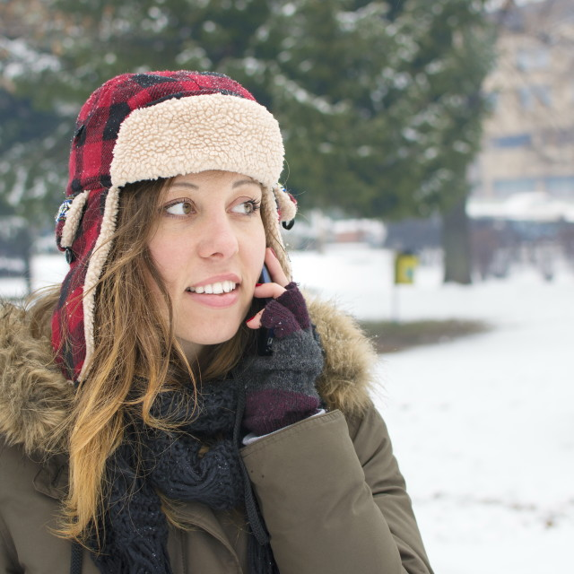 """""""girl with a lumberjack hat talking on her cellphone"""" stock image"""