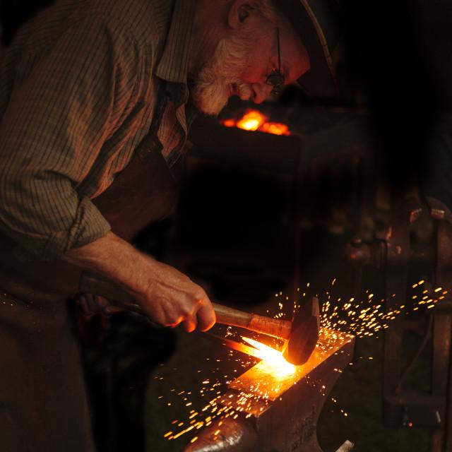 """Blacksmith working at his anvil"" stock image"