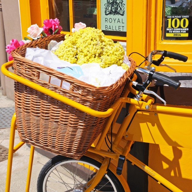 """""""Bicycle with wicker basket full of flowers"""" stock image"""