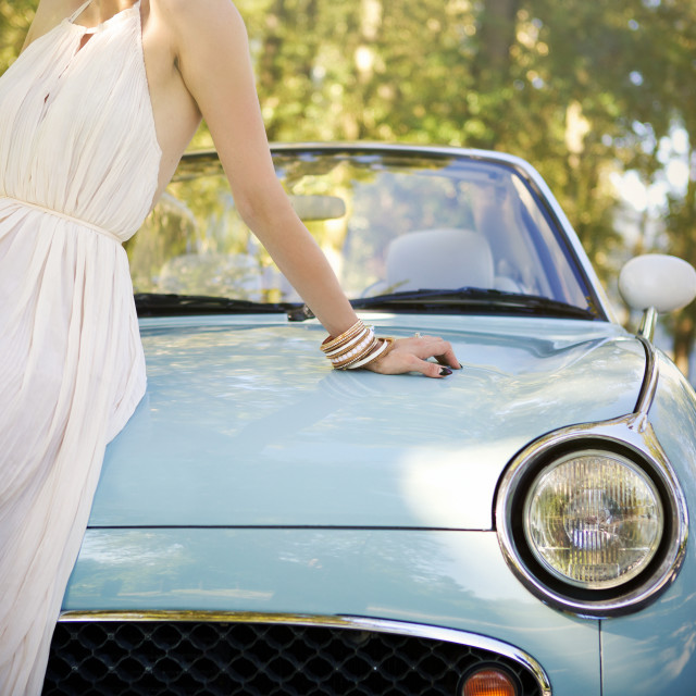 """Portrait of a woman sitting on the hood of her vintage car"" stock image"