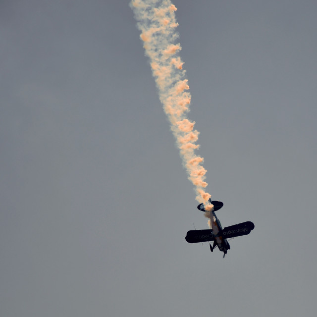 """Plane doing stunts and dropping smoke"" stock image"