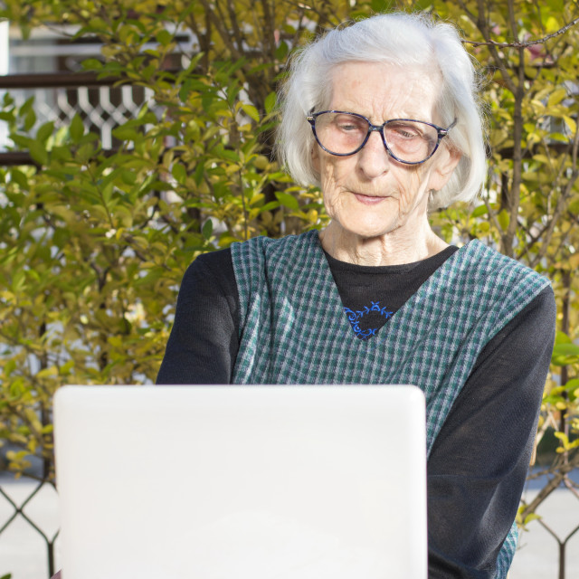 """""""90 years old woman having a video call"""" stock image"""