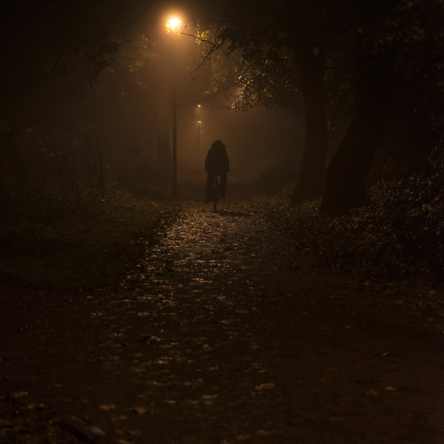 """A lone cyclist in the darkness"" stock image"
