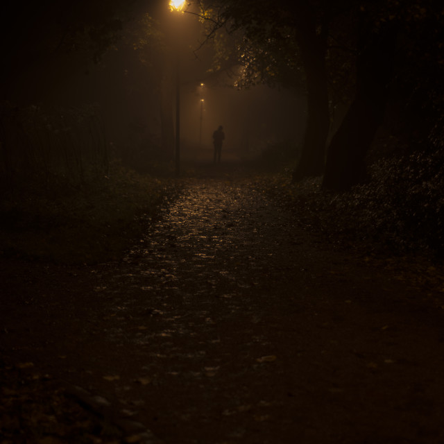"""A lone pedestrian in the darkness"" stock image"