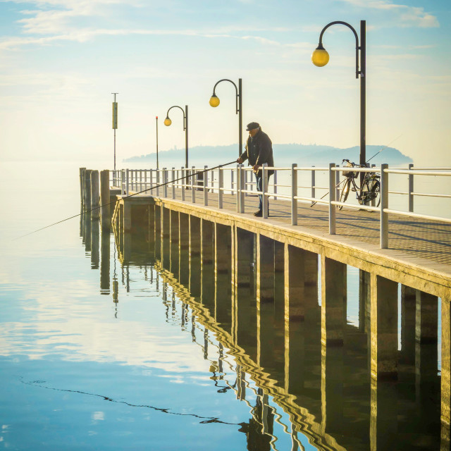 """Pier at Lake Trasimeno and Senior Man Fishing"" stock image"